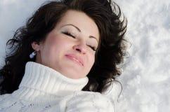 Mujer bonita que miente en nieve. Imagen de archivo