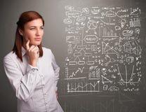 Mujer bonita que mira gráficos y símbolos del mercado de acción Imagen de archivo libre de regalías