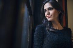 Mujer bonita que mira hacia fuera la ventana Imágenes de archivo libres de regalías