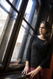 Mujer bonita que mira hacia fuera la ventana Foto de archivo libre de regalías
