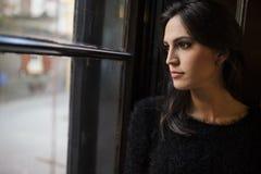 Mujer bonita que mira hacia fuera la ventana Imagenes de archivo