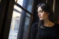 Mujer bonita que mira hacia fuera la ventana Fotos de archivo