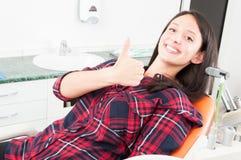 Mujer bonita que muestra el pulgar para arriba en silla del dentista Imagenes de archivo
