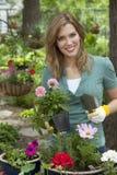Mujer bonita que planta las flores en su jardín Fotos de archivo