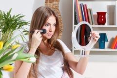 Mujer bonita que pone maquillaje Foto de archivo