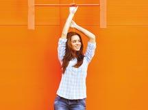 Mujer bonita que presenta cerca de la pared colorida brillante en el estilo urbano Foto de archivo libre de regalías