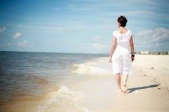 Mujer bonita que recorre la playa Foto de archivo libre de regalías