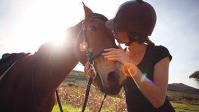 Mujer bonita que se coloca al lado de caballo