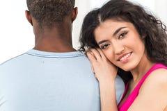 Mujer bonita que se inclina en hombro del hombre y que sonríe en el fondo blanco Imágenes de archivo libres de regalías
