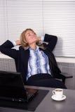 Mujer bonita que se relaja en oficina con una computadora portátil Imágenes de archivo libres de regalías