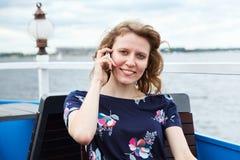 Mujer bonita que se sienta con el teléfono móvil Foto de archivo
