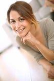 Mujer bonita que se sienta con la mano debajo de la barbilla Foto de archivo