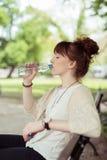 Mujer bonita que se sienta en el agua potable del banco Imagen de archivo