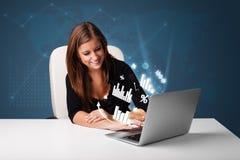 Mujer bonita que se sienta en el escritorio y que pulsa en la computadora portátil con los diagramas Fotografía de archivo