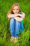 Mujer bonita que se sienta en hierba verde Fotografía de archivo