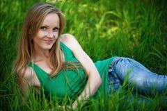 Mujer bonita que se sienta en hierba verde Fotos de archivo libres de regalías