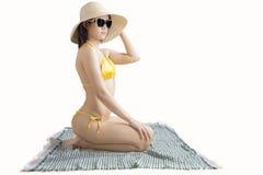 Mujer bonita que se sienta en la estera con el bikini Imagenes de archivo