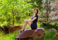 Mujer bonita que se sienta en la roca Imagen de archivo libre de regalías