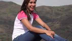 Mujer bonita que se sienta en montañas almacen de metraje de vídeo