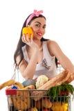 Mujer bonita que se sienta en una carretilla del supermercado Foto de archivo libre de regalías