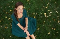 Mujer bonita que se sienta en una hierba foto de archivo