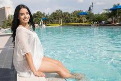 Mujer bonita que se sienta por la piscina Imagenes de archivo