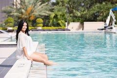 Mujer bonita que se sienta por la piscina Foto de archivo libre de regalías