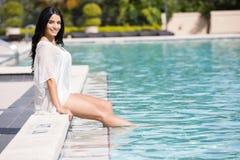 Mujer bonita que se sienta por la piscina Fotografía de archivo libre de regalías