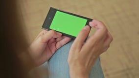 Mujer bonita que sostiene el teléfono elegante con la pantalla de visualización y el tacto verdes metrajes