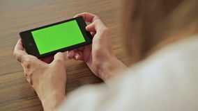 Mujer bonita que sostiene el teléfono elegante disponible con la pantalla de visualización verde almacen de video