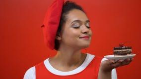 Mujer bonita que sostiene a mano la torta de chocolate con la cereza en el top, disfrutando del aroma almacen de video