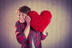 Mujer bonita que sostiene una almohada del corazón Fotos de archivo libres de regalías