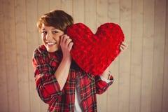 Mujer bonita que sostiene una almohada del corazón Fotografía de archivo libre de regalías