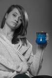 Mujer bonita que sueña despierto sosteniendo una taza azul de la camiseta Imagen de archivo libre de regalías