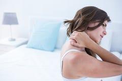 Mujer bonita que sufre de dolor de cuello Foto de archivo