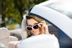 Mujer bonita que toma las gafas de sol apagado en el coche Foto de archivo libre de regalías