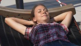Mujer bonita que toma una siesta en hamaca en parque de la ciudad almacen de video