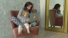 Mujer bonita que usa el ordenador portátil con el pequeño bebé en sus rodillas metrajes