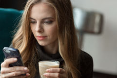 Mujer bonita que usa el teléfono celular y bebiendo cofee Fotografía de archivo libre de regalías