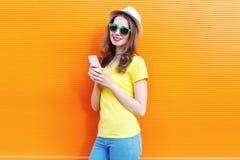 Mujer bonita que usa smartphone sobre naranja colorida Fotografía de archivo libre de regalías