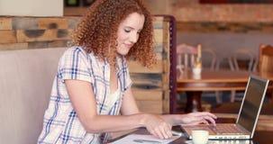 Mujer bonita que usa su ordenador portátil y teniendo llamada de teléfono almacen de video