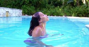 Mujer bonita que viene a la superficie en una piscina almacen de video