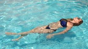Mujer bonita rubia que goza del agua en la piscina Visión desde arriba Cámara lenta almacen de metraje de vídeo