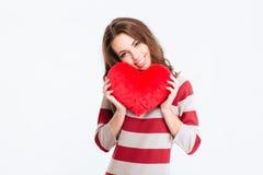 Mujer bonita sonriente que lleva a cabo el corazón rojo Imagen de archivo libre de regalías