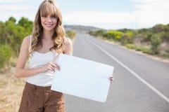 Mujer bonita sonriente que lleva a cabo la muestra mientras que hace autostop Fotografía de archivo