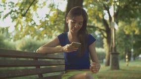 Mujer bonita sonriente que manda un SMS en el teléfono móvil en parque almacen de metraje de vídeo