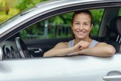 Mujer bonita sonriente que se inclina en la ventanilla del coche Imagen de archivo libre de regalías
