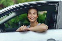 Mujer bonita sonriente que se inclina en la ventanilla del coche Fotos de archivo