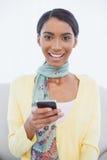 Mujer bonita sonriente que se sienta en envío de mensajes de texto del sofá Imagen de archivo libre de regalías