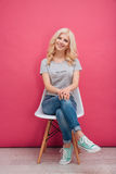 Mujer bonita sonriente que se sienta en la silla Foto de archivo libre de regalías